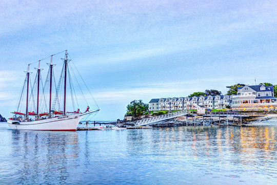 Bar Harbor, USA - June 8, 2017: View of dock and hotel in downtown village in summer during sunset twilight with reflection of yellow illuminated lights and Margaret Todd windjammer large sailboat