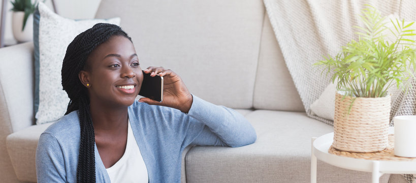 Smiling black girl talking on cellphone with friend at home