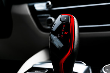 Automatic gear stick of a modern car. Modern car interior details. Close up view. Car detailing. Automatic transmission lever shift. White leather interior with stitching