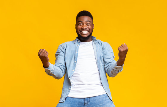 Portrait of overjoyed black man celebrating success with clenched fists