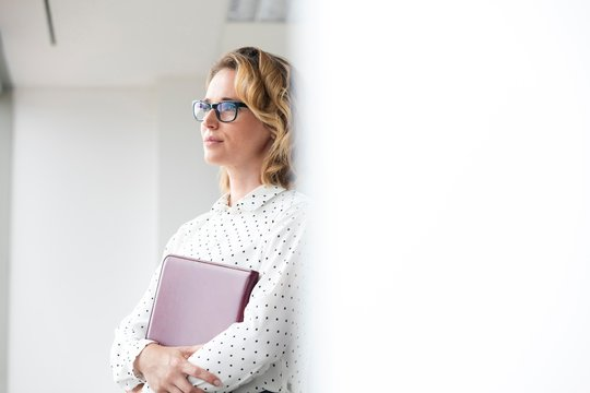 Thoughtful businesswoman looking through the window in office