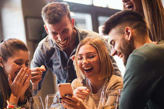 Group of young friends having fun in restaurant talking, laughing while dining at table and making selfie.
