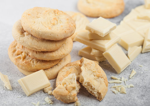 White chocolate biscuit cookies with chocolate blocks and curls on light kitchen table background.