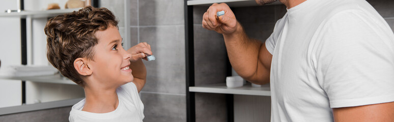 panoramic shot of kid holding toothbrush and looking at father in bathroom