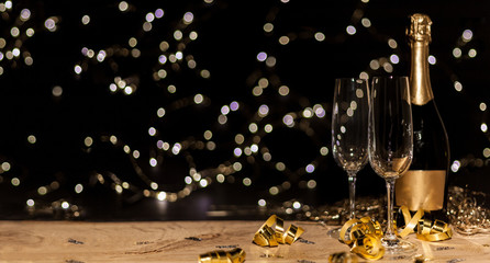 Foto auf AluDibond Alkohol New Year's Eve background with champagne bottle and glasses confetti and gold snakes New Year's Eve background with confetti and gold snakes on wooden table, lights