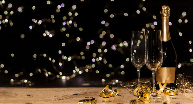 New Year's Eve background with champagne bottle and glasses confetti and gold snakes New Year's Eve background with confetti and gold snakes on wooden table, lights