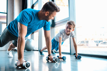 Keuken foto achterwand Fitness happy father looking at cheerful son and exercising with dumbbells