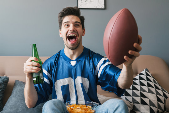 Photo of man screaming and drinking beer while watching sports match