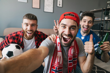 Photo of excited guys fans showing thumb up and taking selfie photo