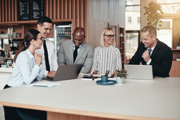 Diverse group of laughing businesspeople working in an office