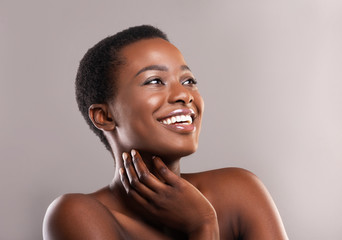 Beautiful nude african girl touching her soft skin and smiling