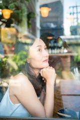 Beautiful asian women sitting in urban coffee shop looking out of window