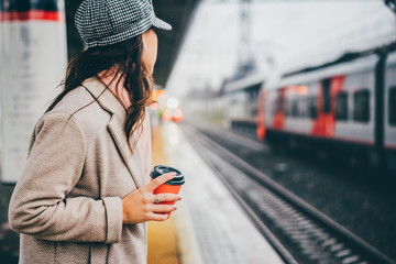 Woman holding red cup and drinking coffee during waiting the train at the station.