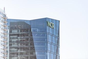 Atlanta, USA - April 20, 2018: Capital Georgia city, view of building with NCR sign, global headquarters, modern glass building