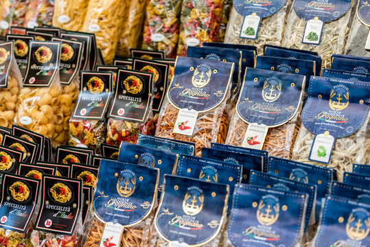 Rome, Italy - September 4, 2018: Italian street food market with closeup of many packaged dry pasta souvenirs, outside in historic city, colorful