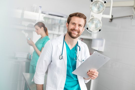 Smiling Confident doctor reading results in clinic