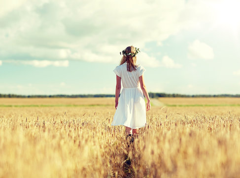 happiness, nature, summer holidays, vacation and people concept - smiling young woman in wreath of flowers and white dress walking along cereal field