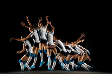 Young female volleyball player isolated on black studio background. Woman in sport's equipment and...