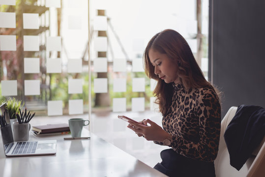Attractive young asian businesswoman sitting using app on smartphone at office.