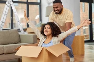 moving, repair and real estate concept - happy african american couple having fun and playing with cardboard box at new home