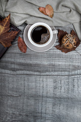 Cup of black coffee with chocolate cookies surrounded by autumn leaf and notebook on a wooden table