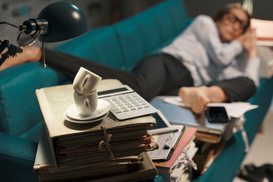 Stressed businesswoman sleeping on a couch with lots of paperwork