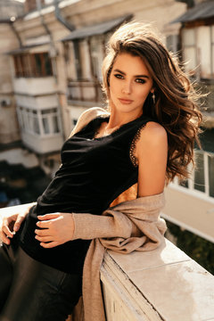 beautiful sexy woman in elegant clothes posing in balcony with city view