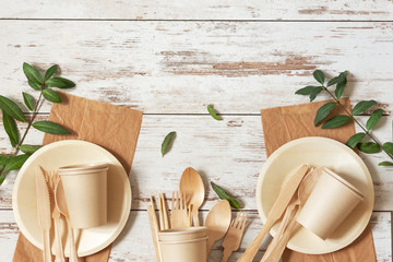 Eco friendly disposable dishes made of bamboo wood and paper on white wooden background.