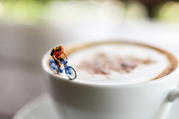 Miniature people : Coffee cup with cycling, image use for charge your energy in the morning