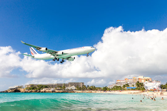 PHILIPSBURG, SINT MAARTEN - DECEMBER 13, 2016: Airfrance commercial airplane approaches Princess Juliana airport above onlooking spectators on Maho beach.