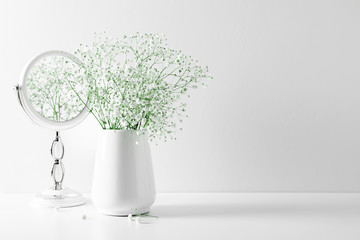 Elegant floral soft white composition, mirror, white flowers. Beautiful white gypsophila flower in vase on white wall background.