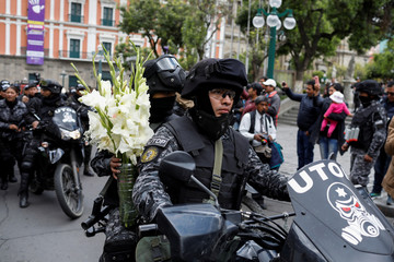 A member of the security forces carries flowers to pay homage to commander Herbert Antelo, at Murillo Square, in La Paz