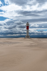 Lighthouse by the sea in the middle of the desert. Brown, blue and gray colors