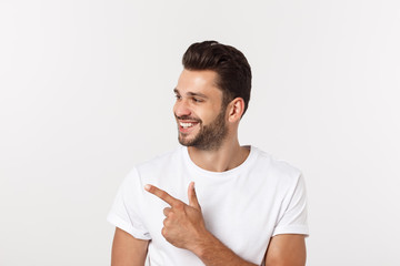 Man pointing showing copy space isolated on white background. Casual handsome Caucasian young man. Wall mural