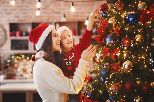 Mother and daughter putting decorations on xmas tree