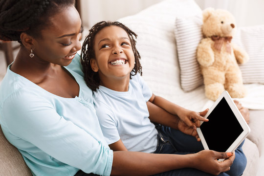 African-american mom and daughter using digital tablet