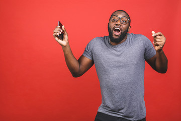 Indoor portrait of young handsome African man isolated on red background during dance to playlist...