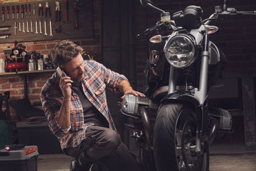 Man talking by the phone kneeling at motorcycle