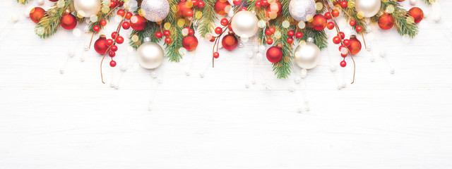 Classic Christmas composition with fir branches and white and red baubles on white wooden...