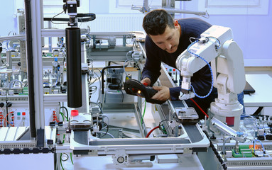 Man is programming robot arm with control panel which is integrated on smart factory production line. industry 4.0 automation line which is equipped with sensors and robotic arm. Selective Focus.