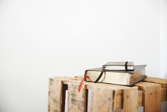 Closeup shot of a bible and notepad on a wooden box with a white background