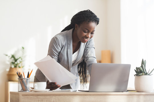 Black Businesswoman Working With Papers And Laptop In Modern Office