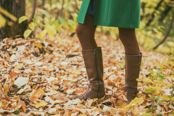 Close up photo of woman in boots surrounded with fall leafs while spending time in the park.