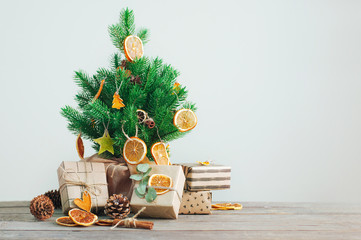 Dried citrus slices on the Christmas tree with craft paper wrapping gift boxes