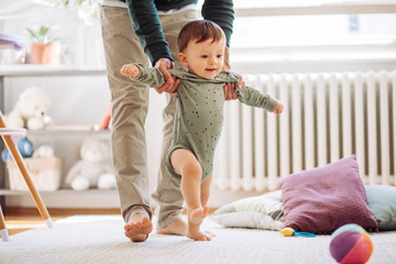 Young father helping baby to practice walking, they are home and enjoy in time they spending together