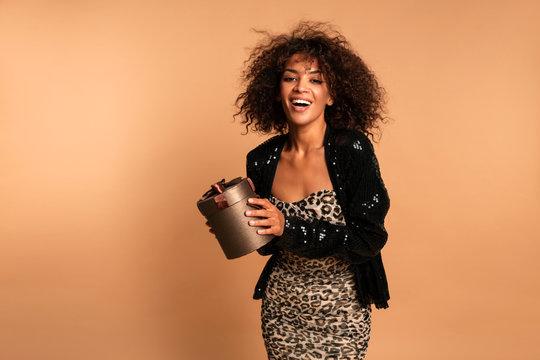 Amazing luxury seductive woman in stylish black leopard party dress posing on beige wall holding present bag . Bright smokey eyes make up. Fashion portrait. Celebrating birthday party.