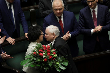 Poland's Law and Justice leader Jaroslaw Kaczynski gives flowers to newly elected Speaker of Parliament Elzbieta Witek during first sitting of Poland's lower house of parliament in Warsaw