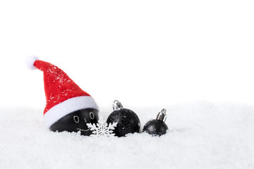 Black Christmas baumle with Santa Hat on snow on white background
