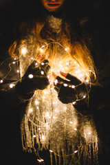 Young woman holding Christmas lights outdoors in the dark