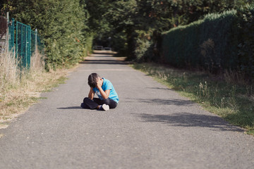 Lost boy sitting on the road crying